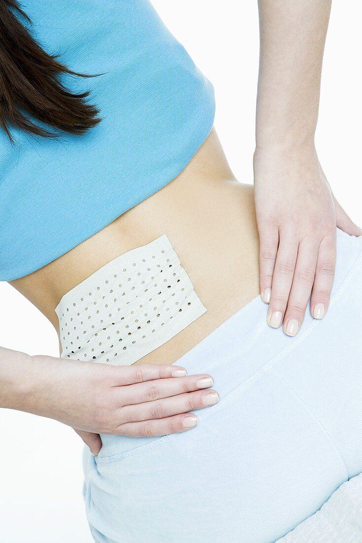 Young woman with pain-relieving plaster on her back