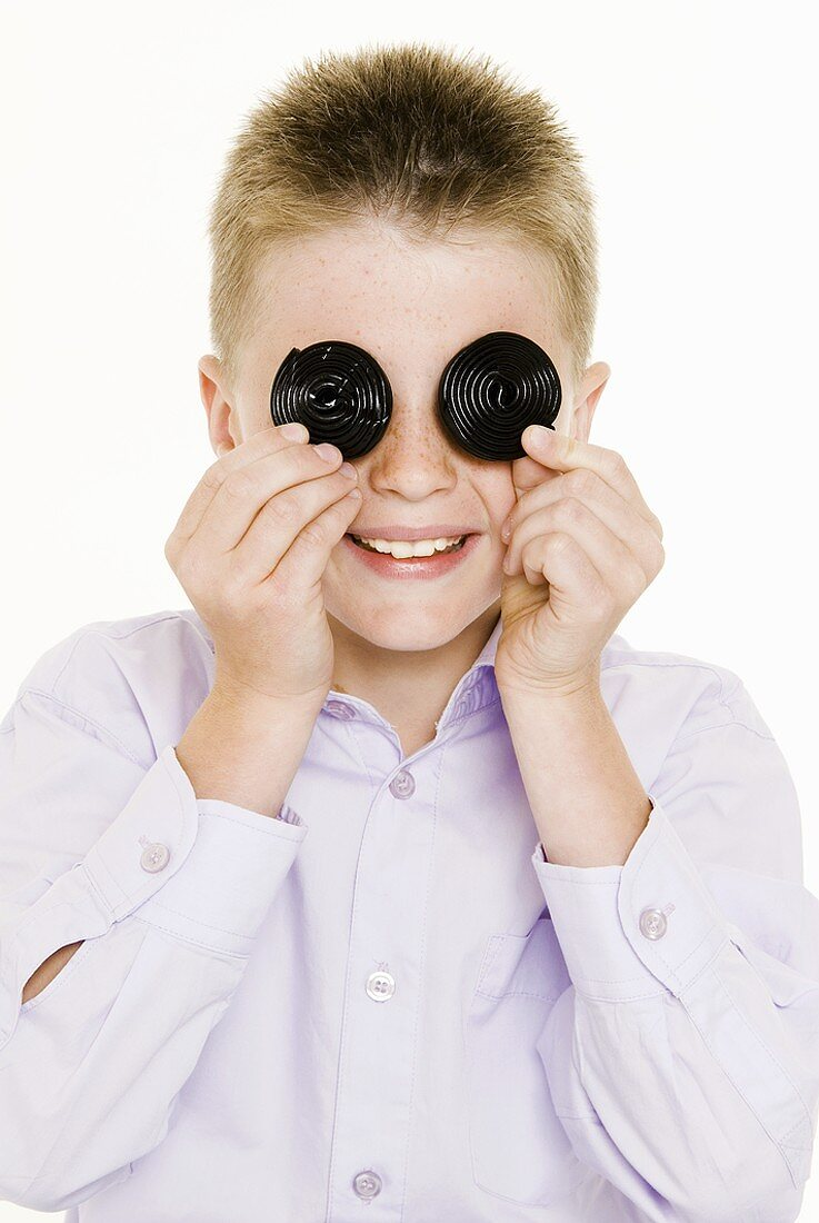 Boy holding two liquorice wheels in front of his eyes