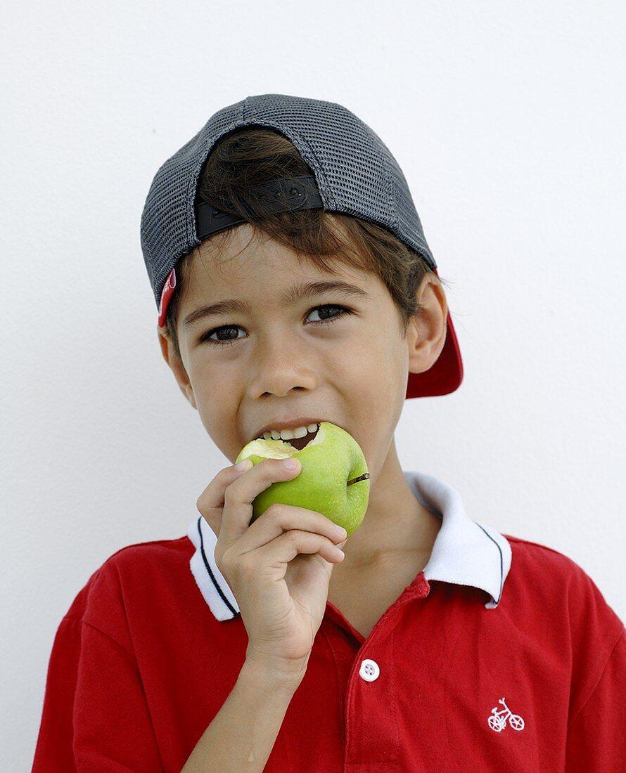Boy biting into an apple