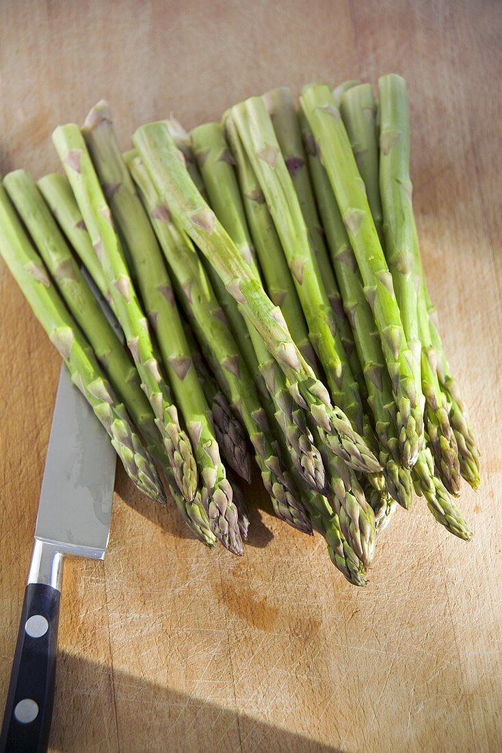Green asparagus and knife on a wooden board