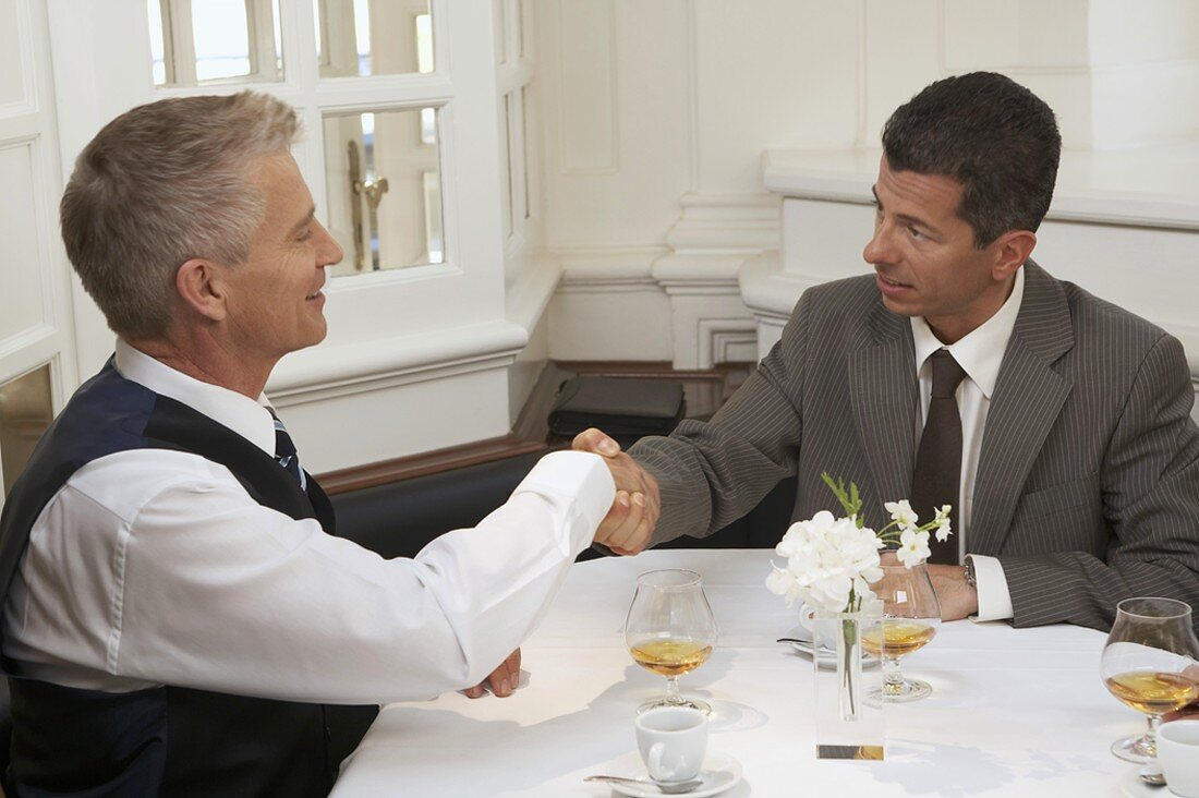 Two businessmen coming to an agreement after a business meal