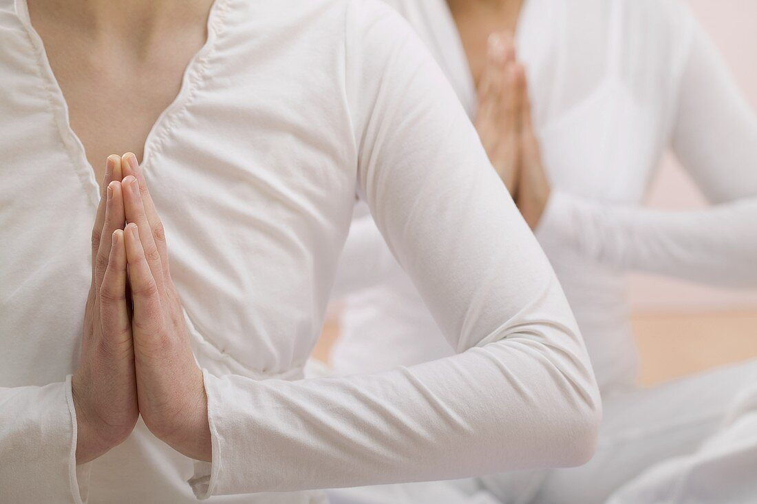 Two young women meditating with hands together