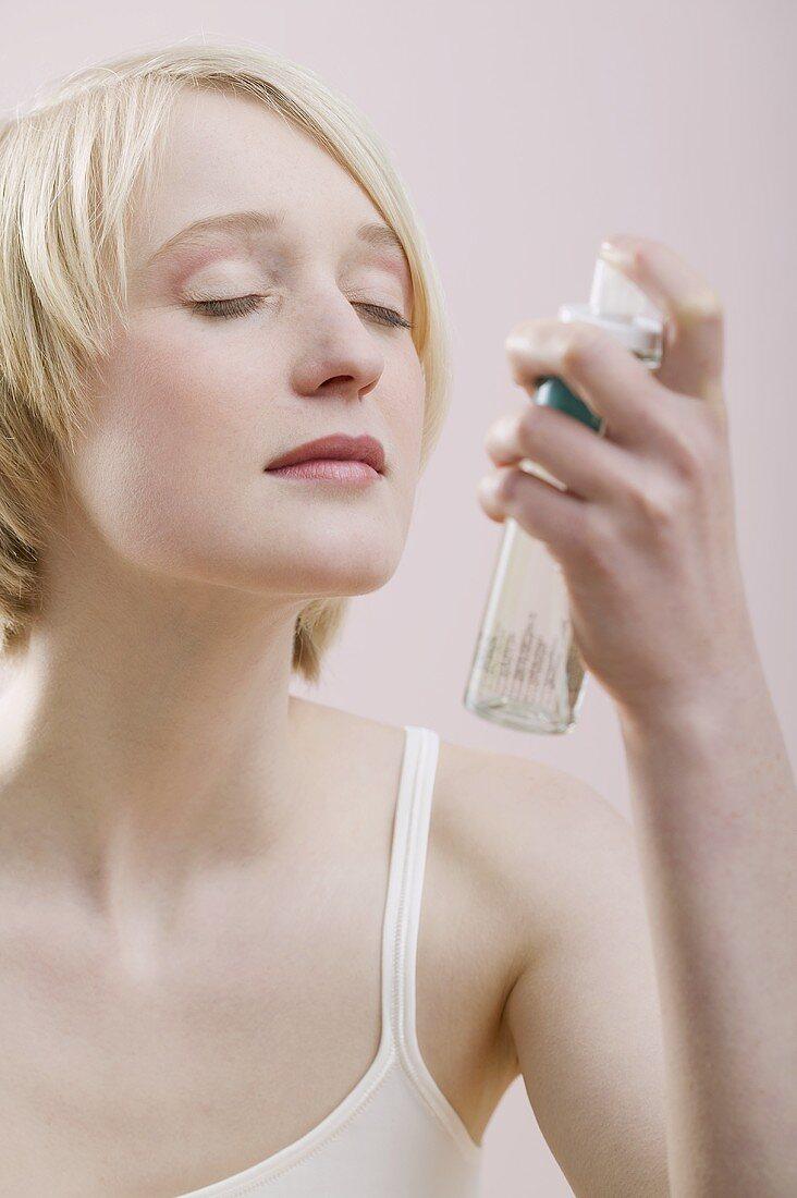 Young woman spraying perfume spray