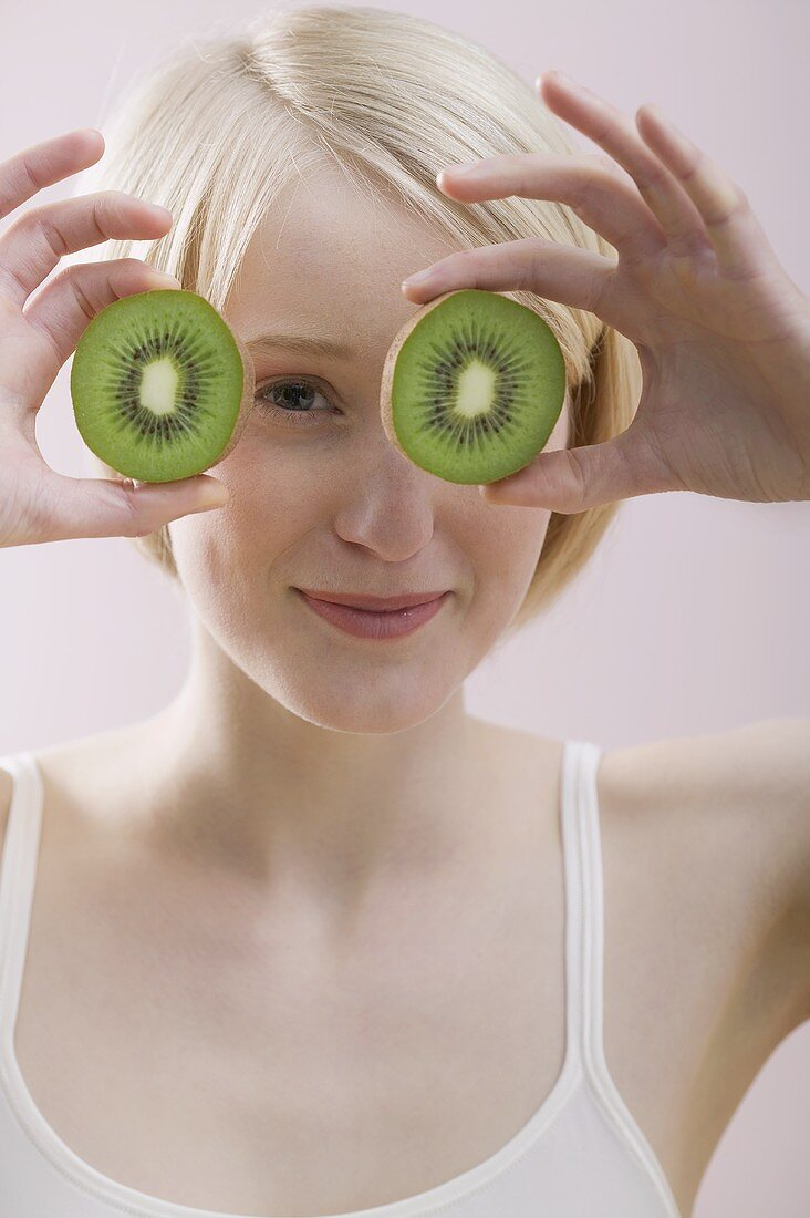 Young woman with two kiwi fruit halves in front of her face