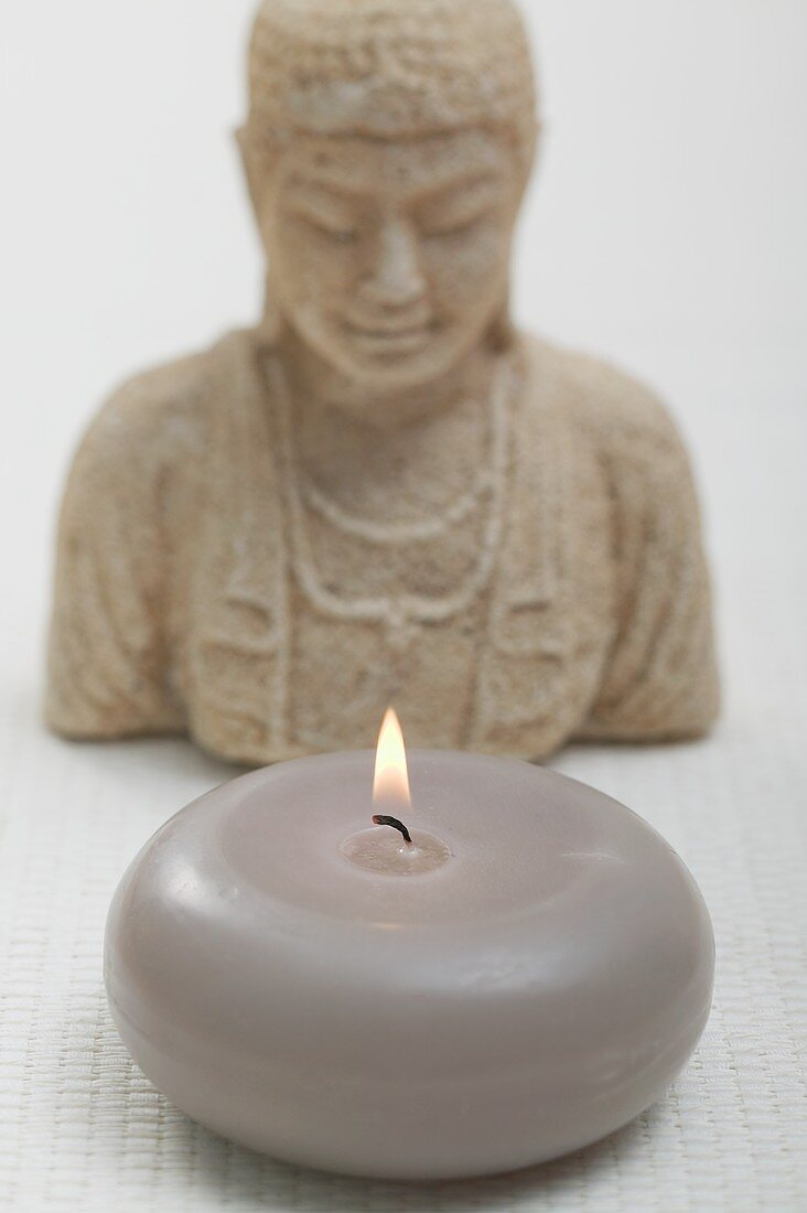 A burning floating candle with religious bust