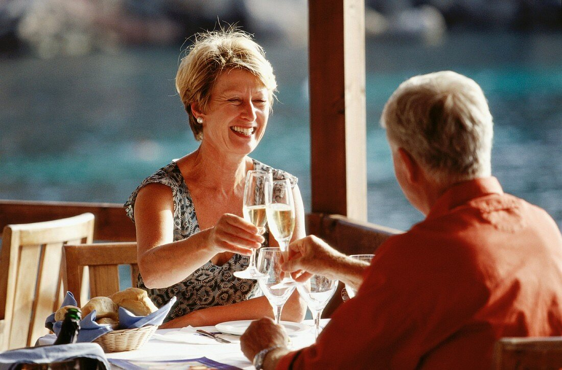 Married couple clinking glasses in restaurant by the sea (Greece)