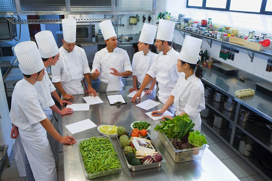 Trainee chefs learning to cook from a head chef