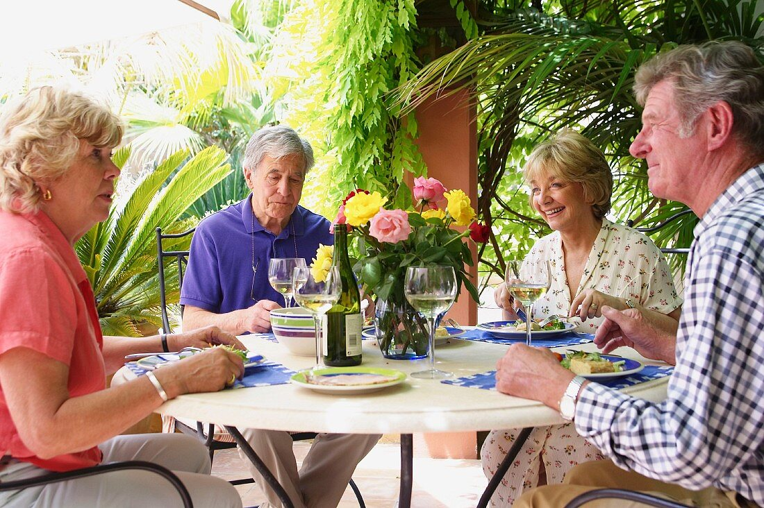 Two older couples sharing a meal on holiday