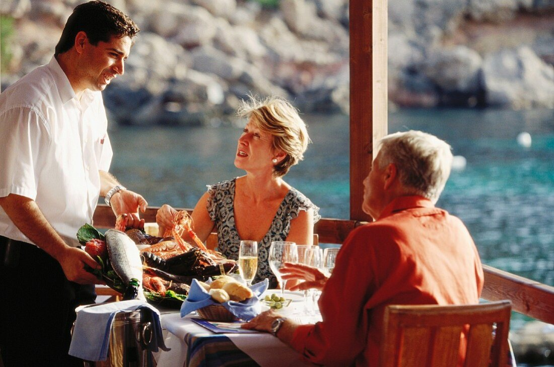 Older married couple dining out on holiday