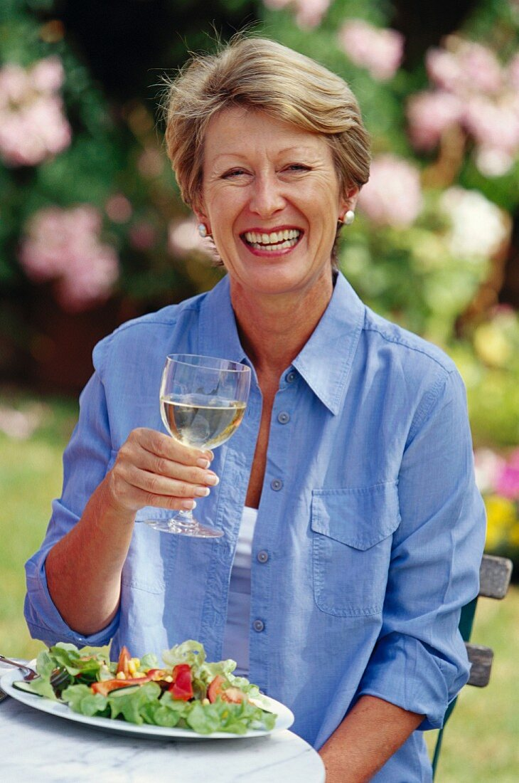 Older woman with salad and glass of white wine