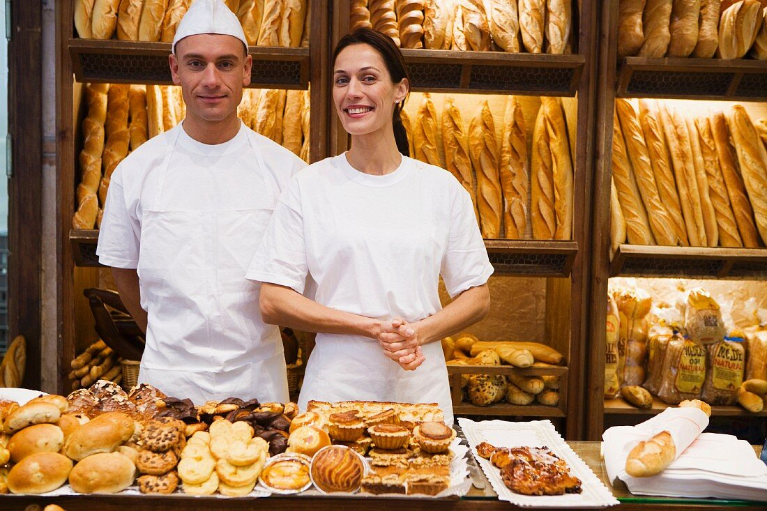 Two shop assistants in bakery with pastries and baguettes