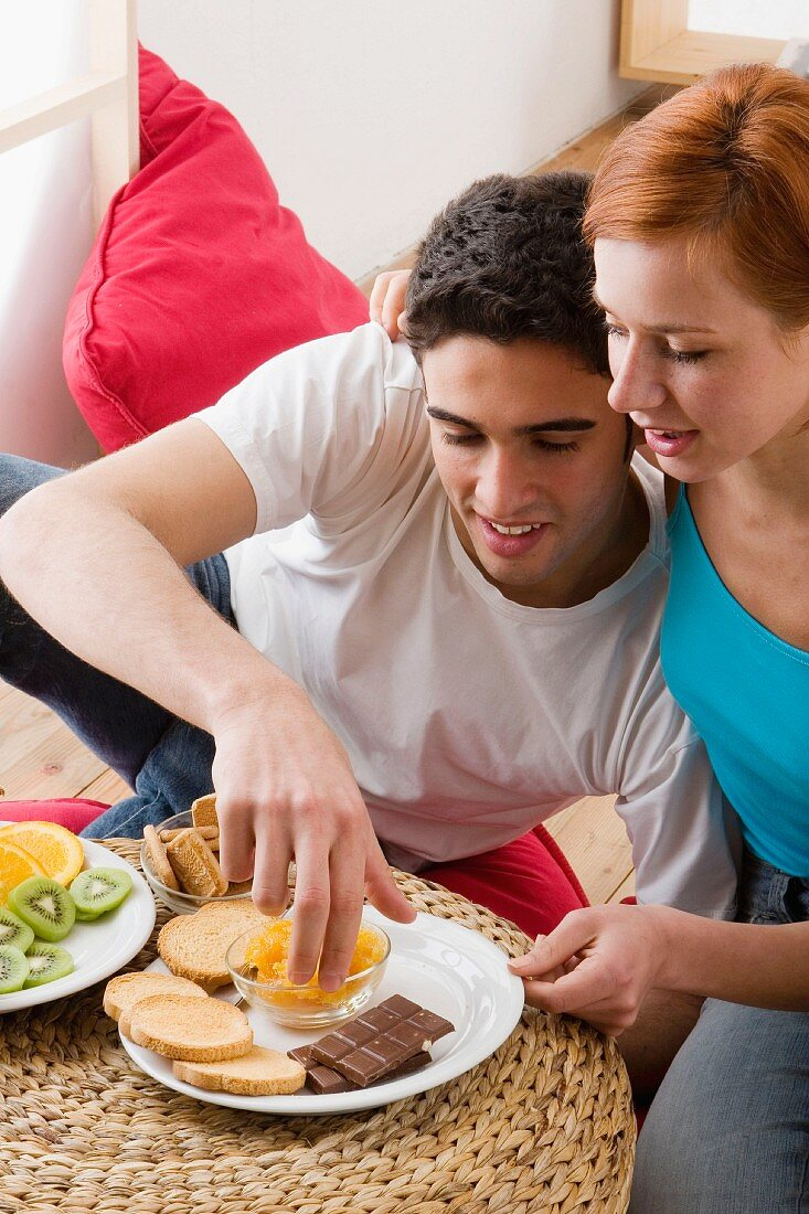 Couple eating fruit, chocolate and rusks in living room