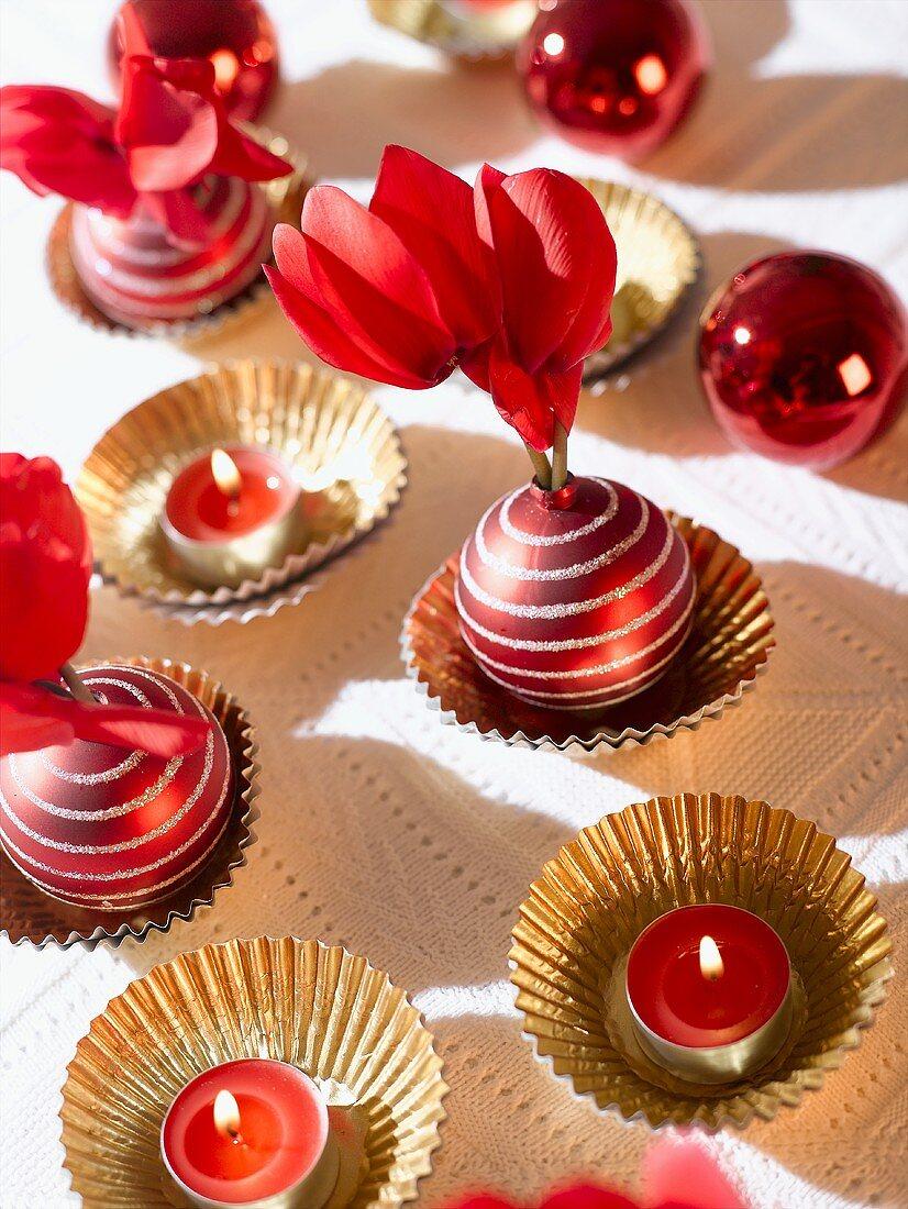 Tischdeko: rote Teelichter, Alpenveilchen, Weihnachtskugeln