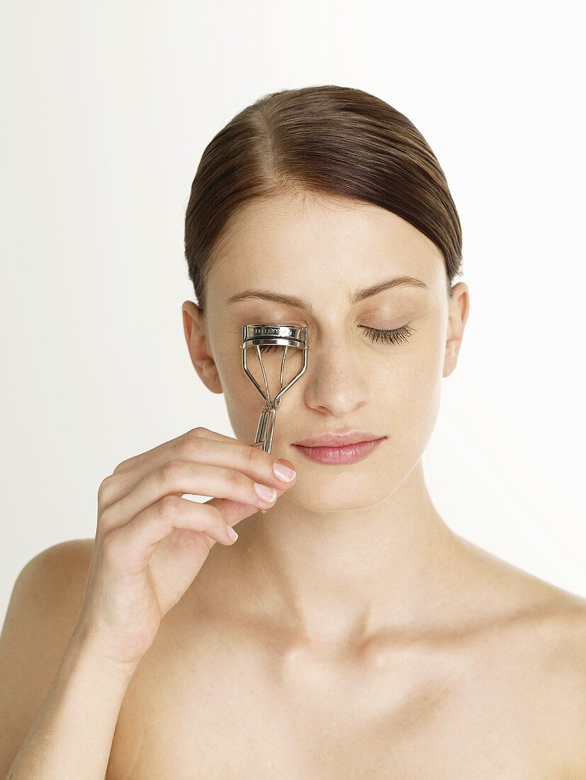 Woman with an eyelash curler