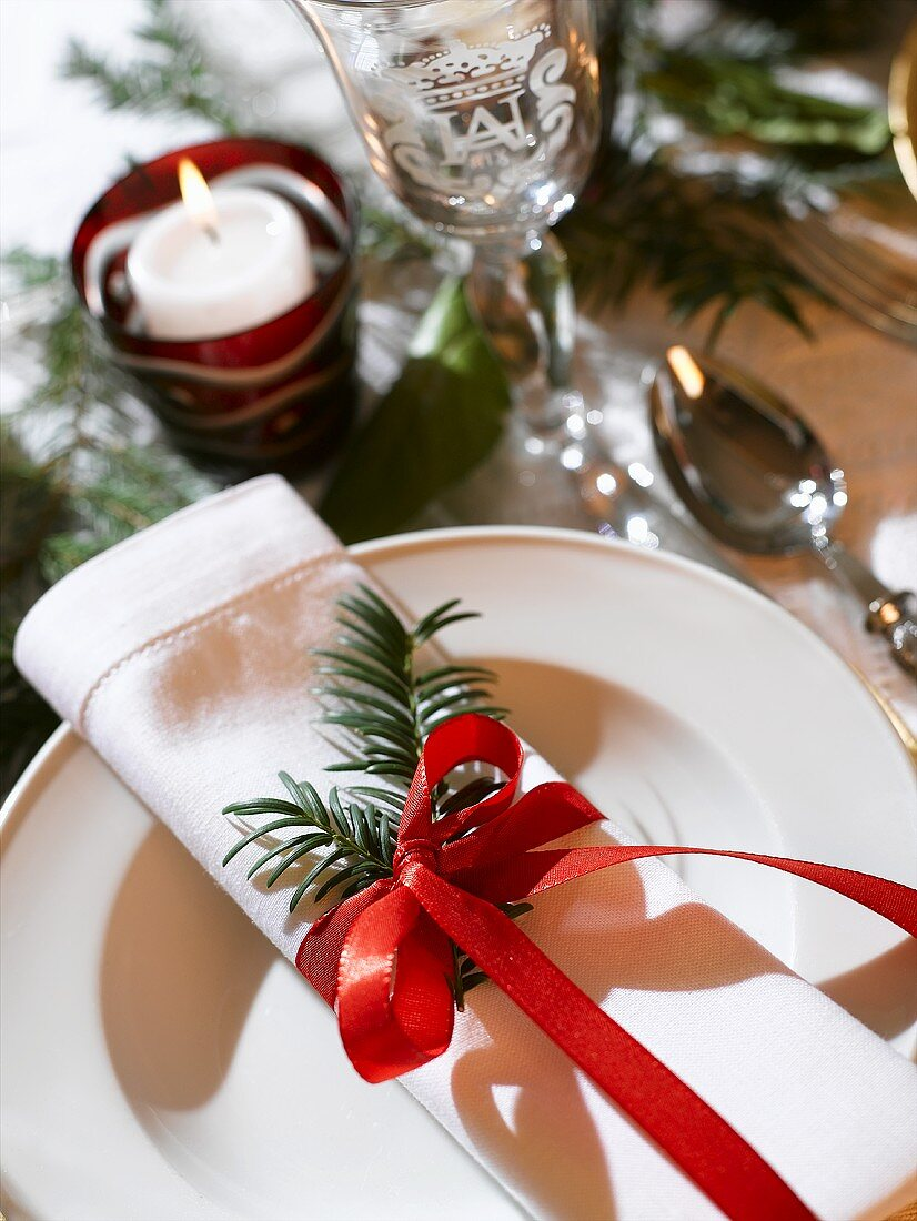 Place-setting with fabric napkin, fir sprig and red bow