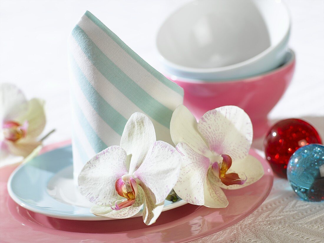 Place-setting with napkin and orchids