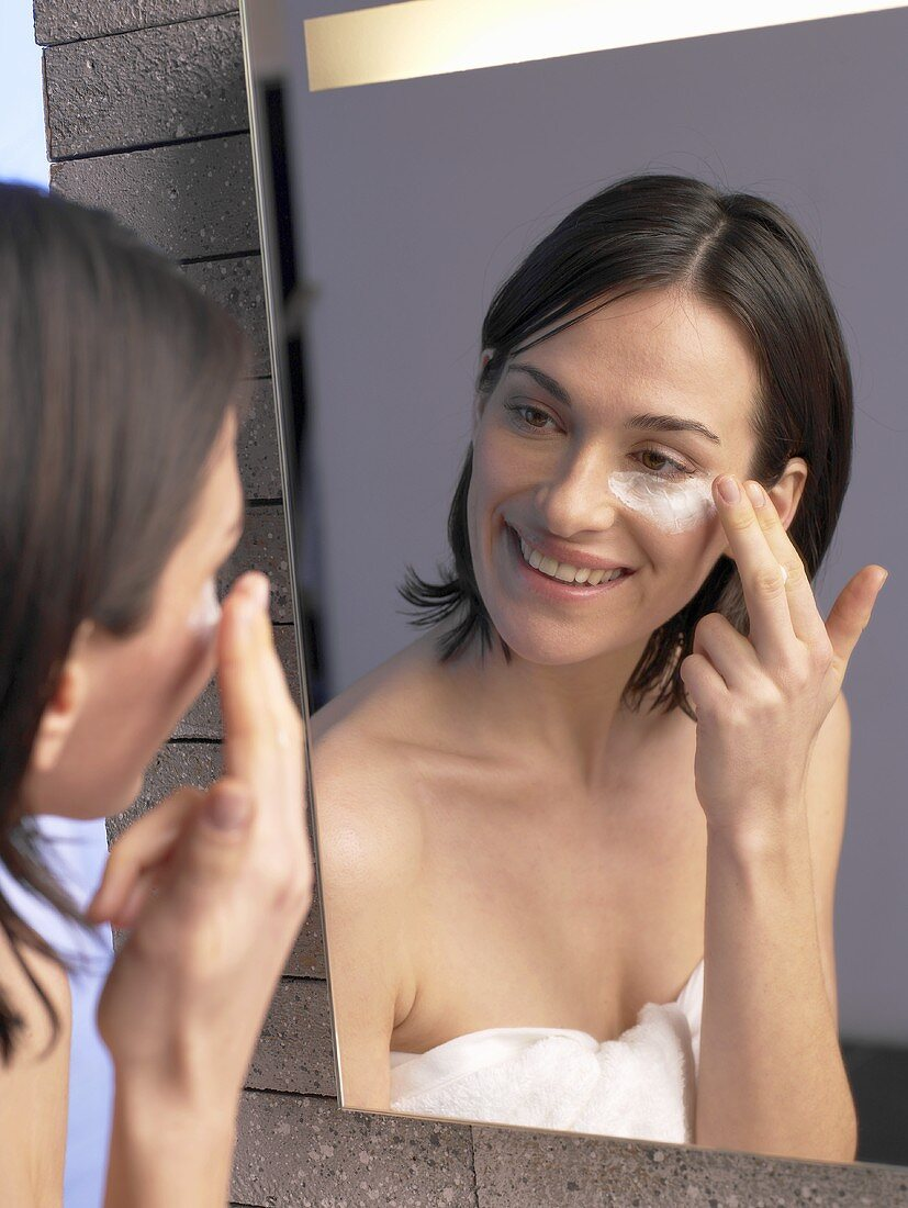 Woman in front of mirror putting cream on her face