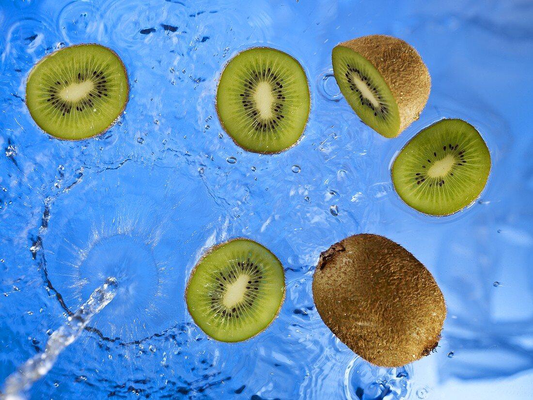 Stream of water running onto kiwi fruit and kiwi fruit slices
