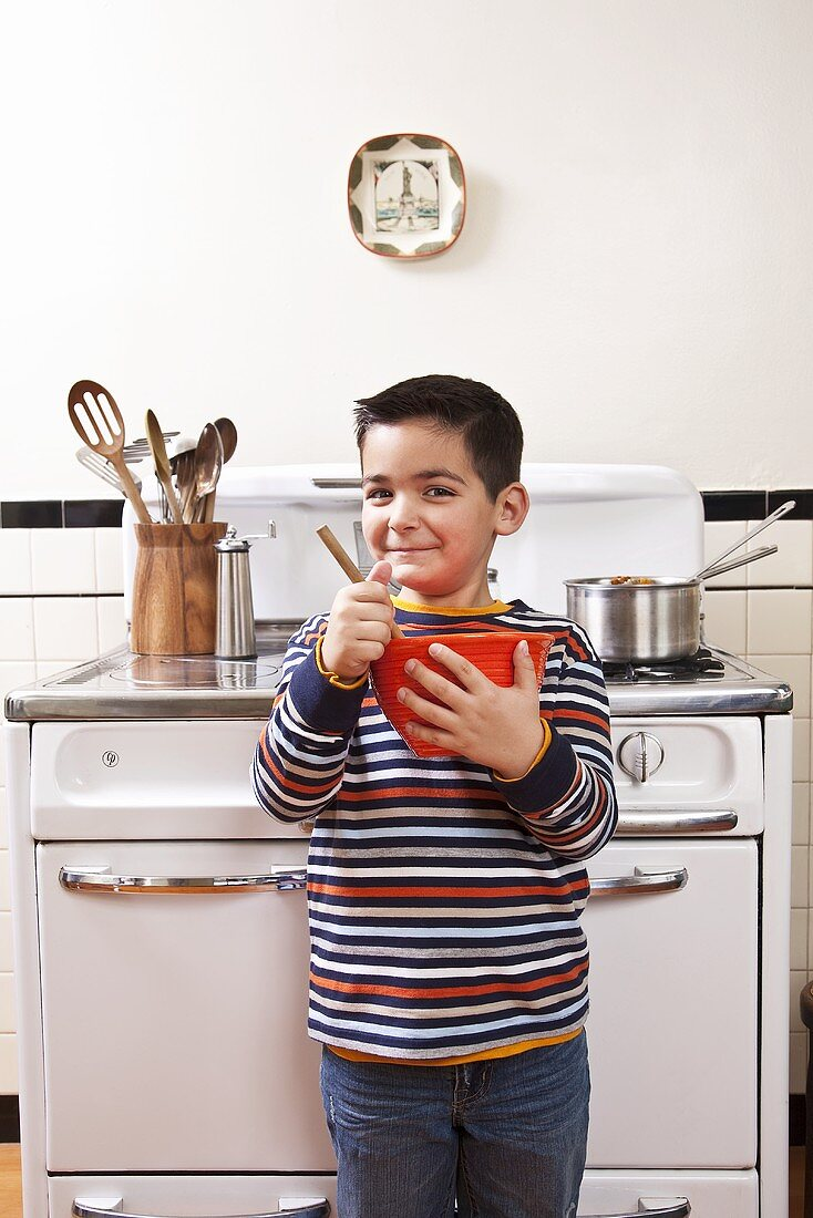 Six Year Old Boy Stirring Bowl In Front of Stove in Kitchen