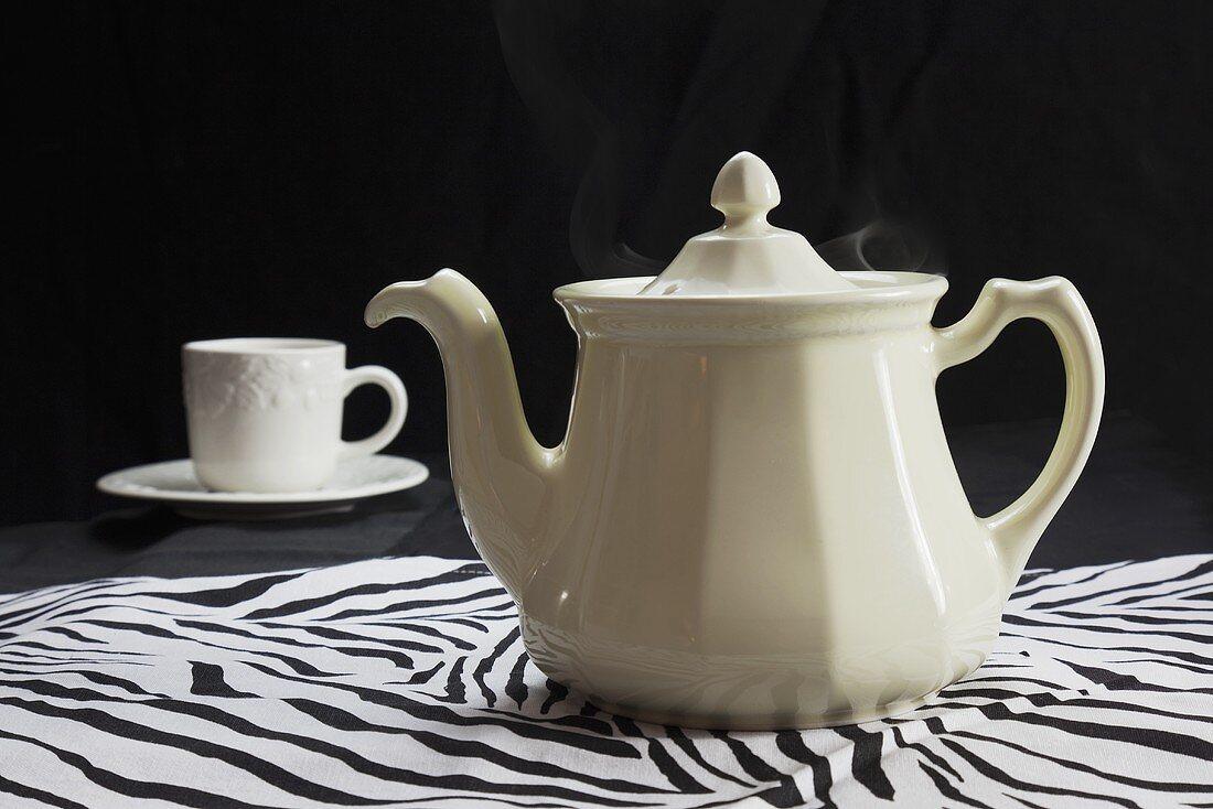 White Tea Pot and Tea Cup on Zebra Pattern Cloth