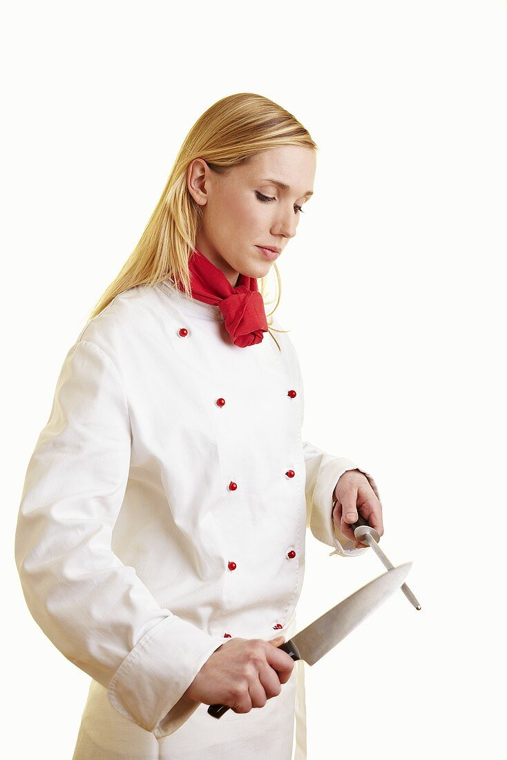 Blond female chef sharpening kitchen knife
