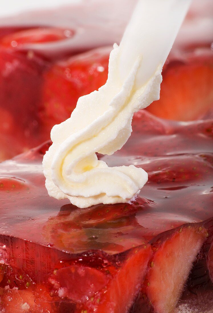 Piping cream onto strawberry cake