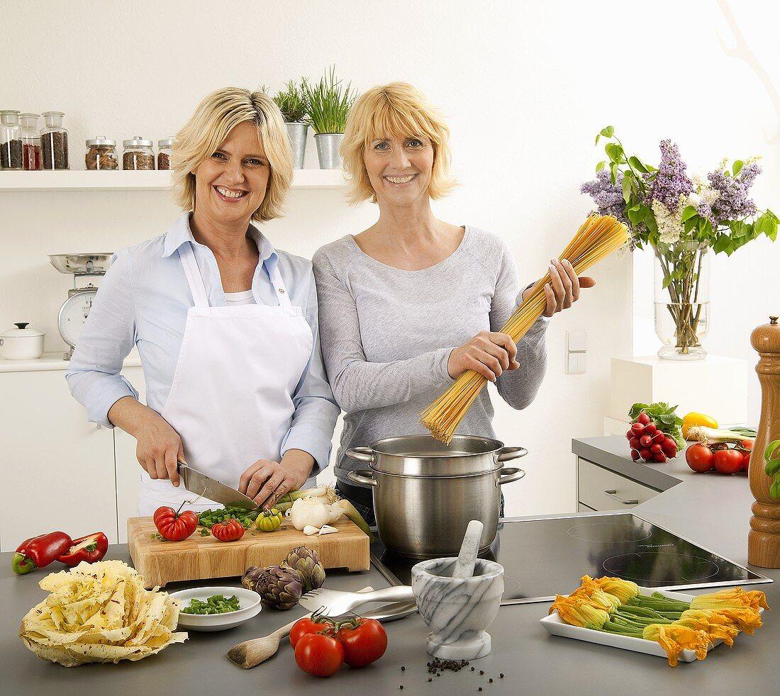 Women having a laugh while cooking spaghetti