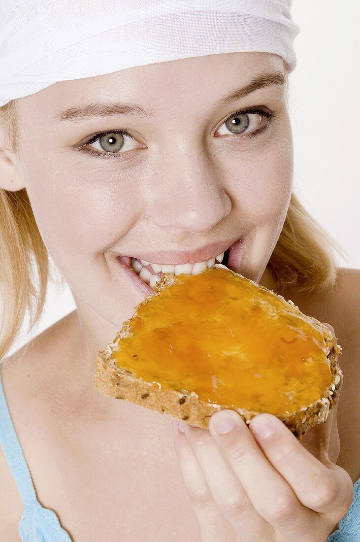 Young woman with headscarf biting into a slice of bread with apricot jam