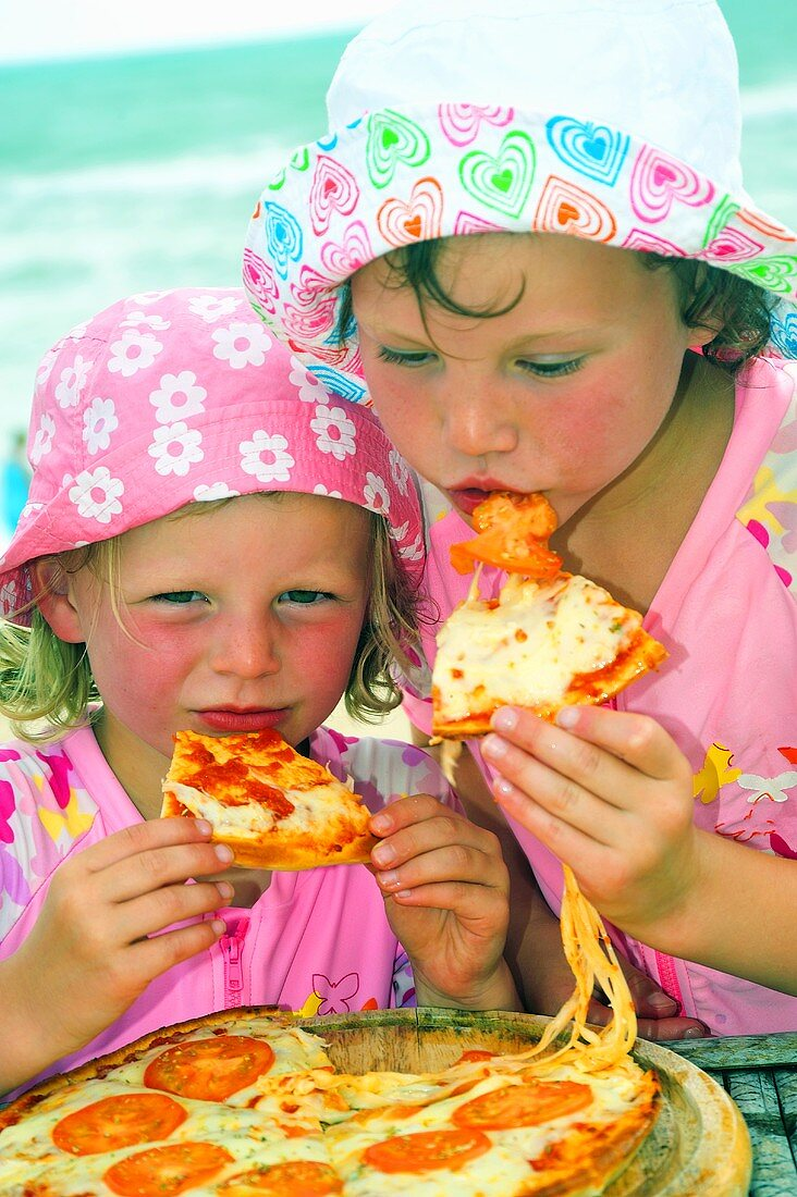 Two children eating pizza on the beach