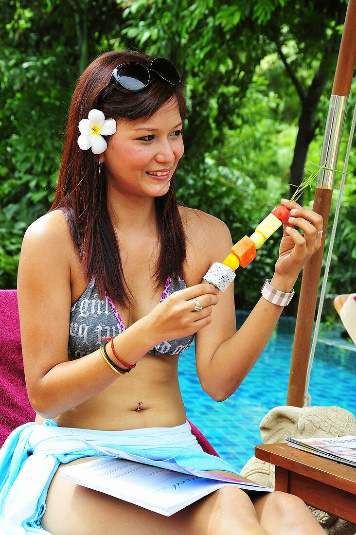 Woman on lounger by pool with fruit skewer
