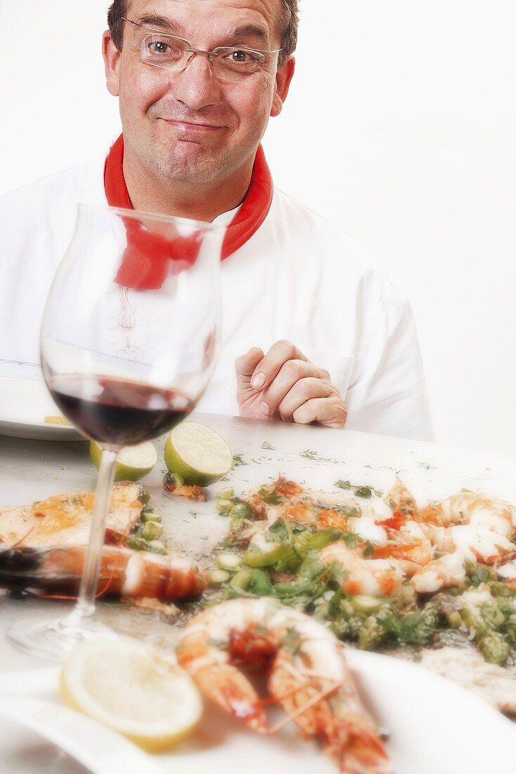 Chef with grilled prawns and glass of red wine