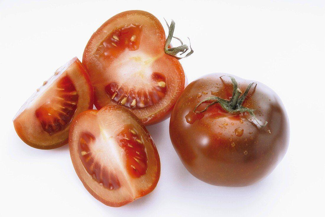 Tomatoes (variety: Kumato), whole, halved and quarter