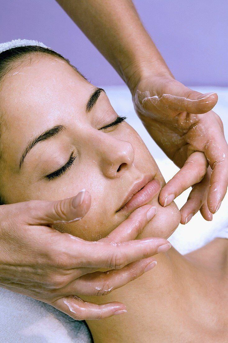 Young woman having cosmetic treatment (facial massage)