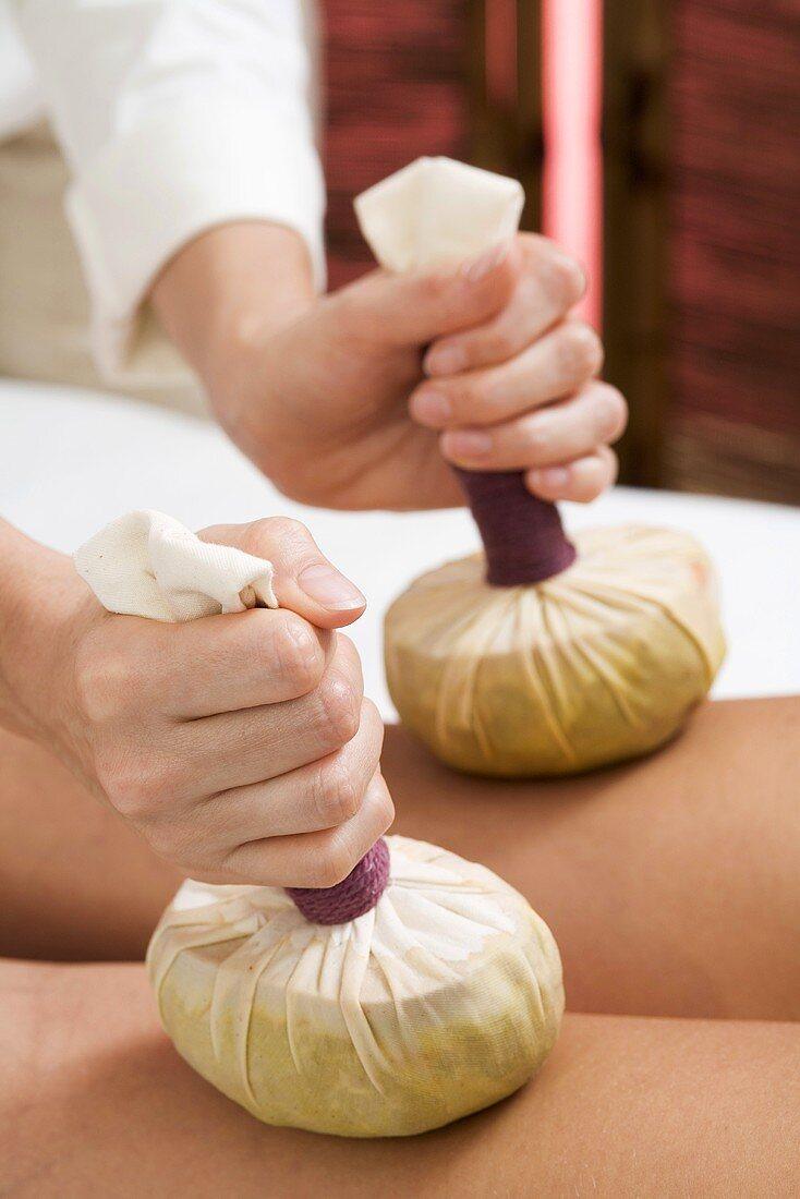 Woman receiving herbal stamp massage