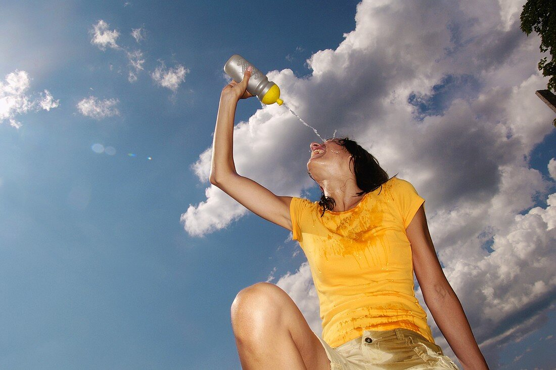 Young woman refreshing herself with mineral water