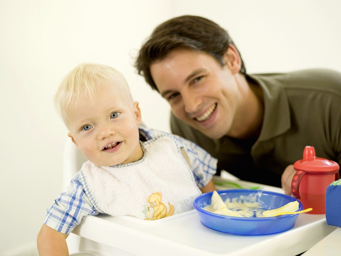 Father with baby eating in high chair