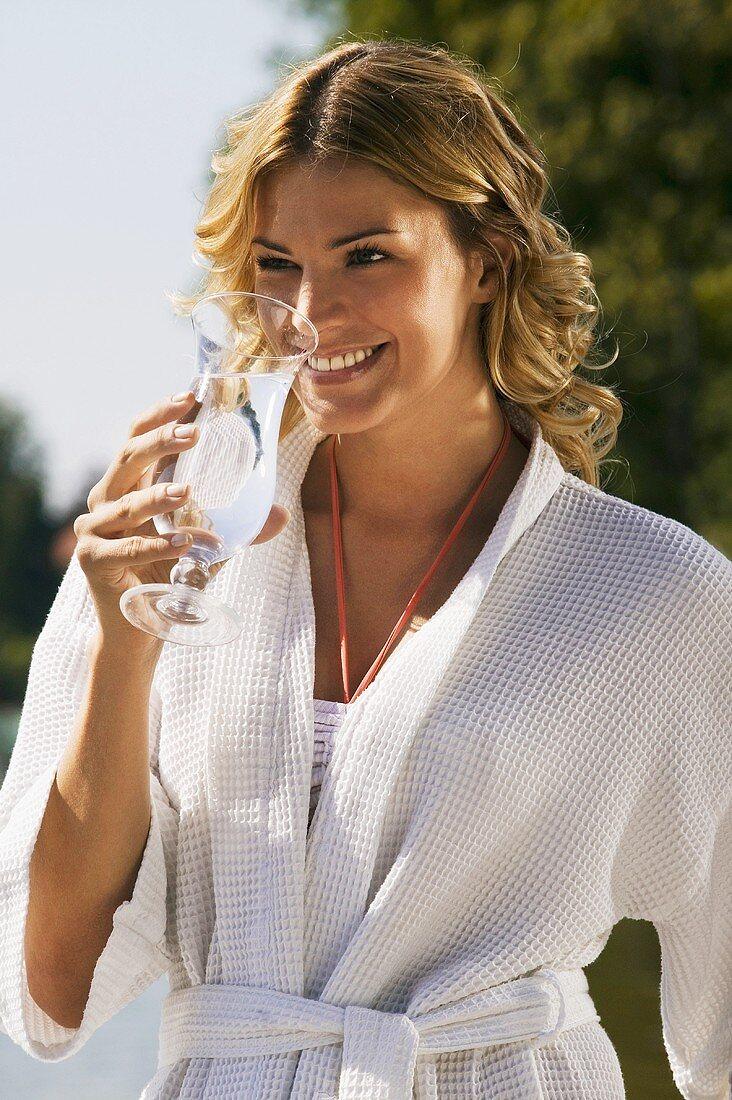 Woman in bathrobe drinking glass of water