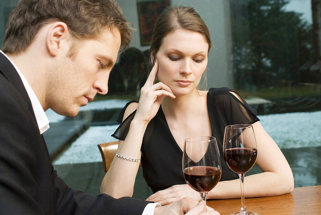Couple drinking red wine looking unhappy