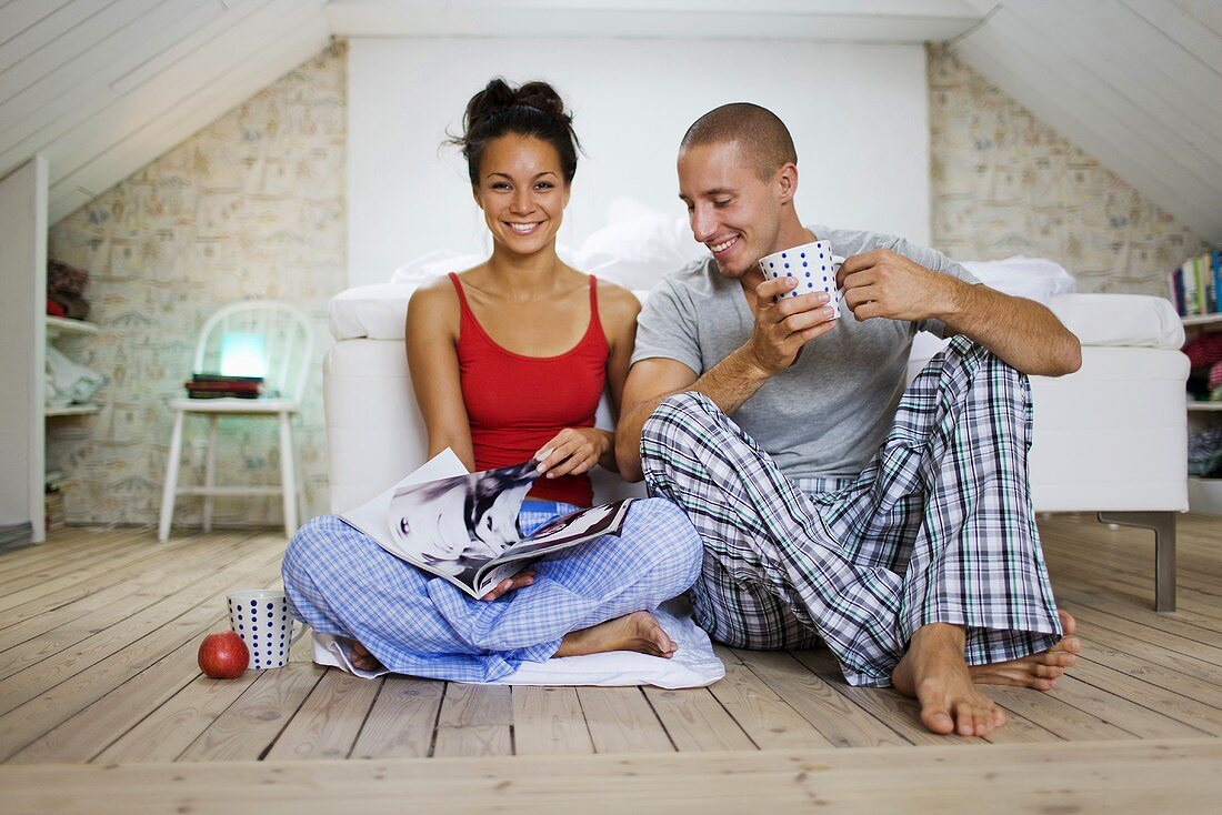 Man and woman sitting on floor in bedroom