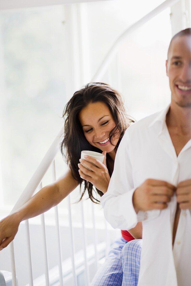 Woman drinking coffee, man putting shirt on