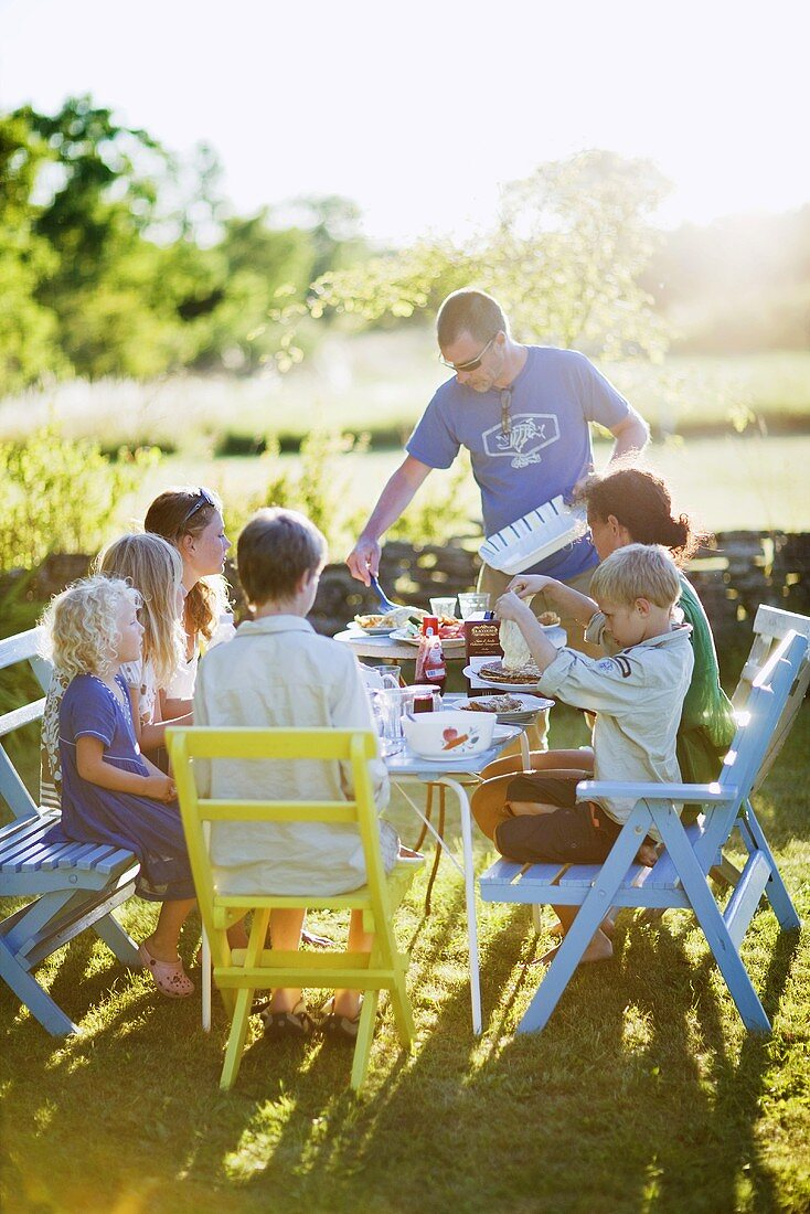 Family with several children eating in garden