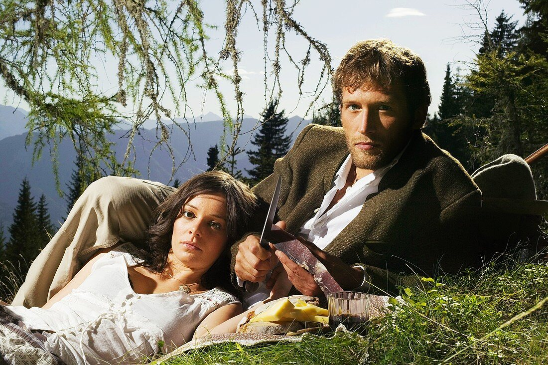 Young couple lying in meadow, having picnic