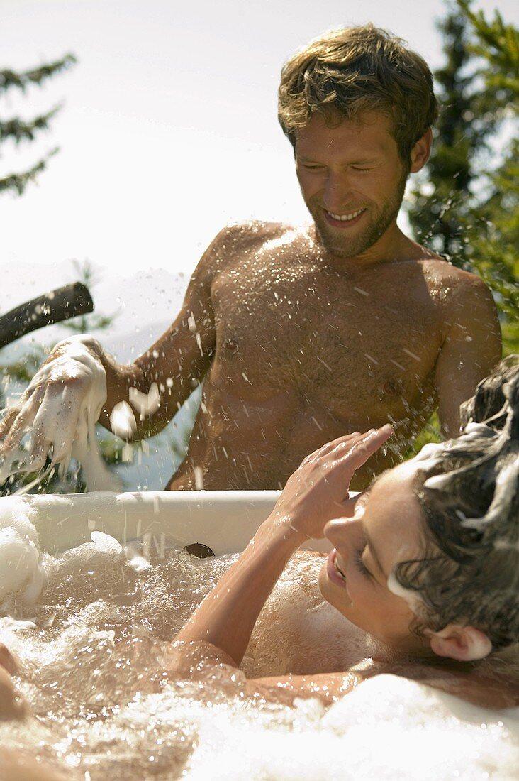 Young couple, woman in tub splashing water