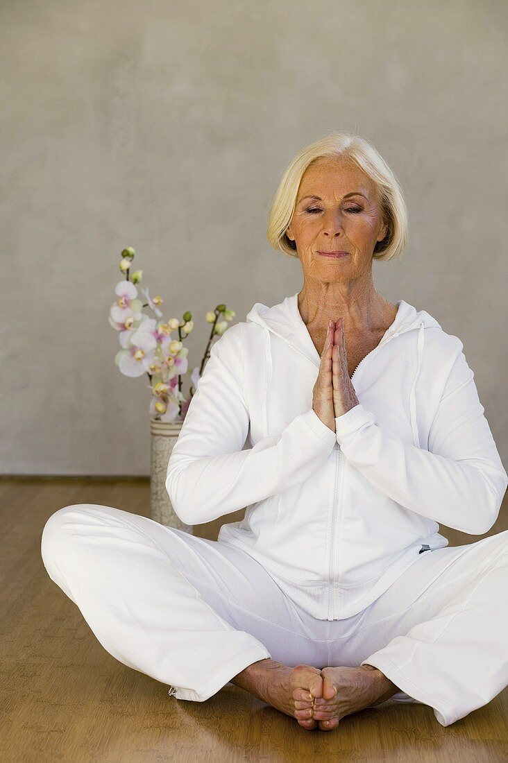 Senior woman with eyes closed in yoga position, smiling