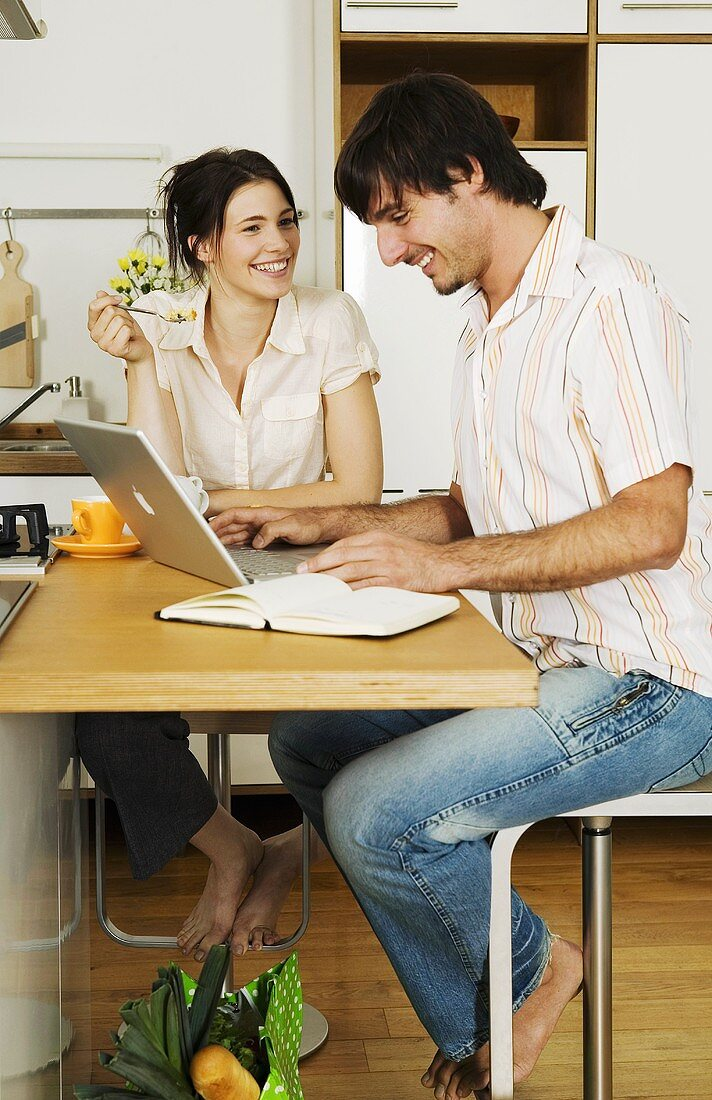 Young couple in kitchen, man using laptop, smiling