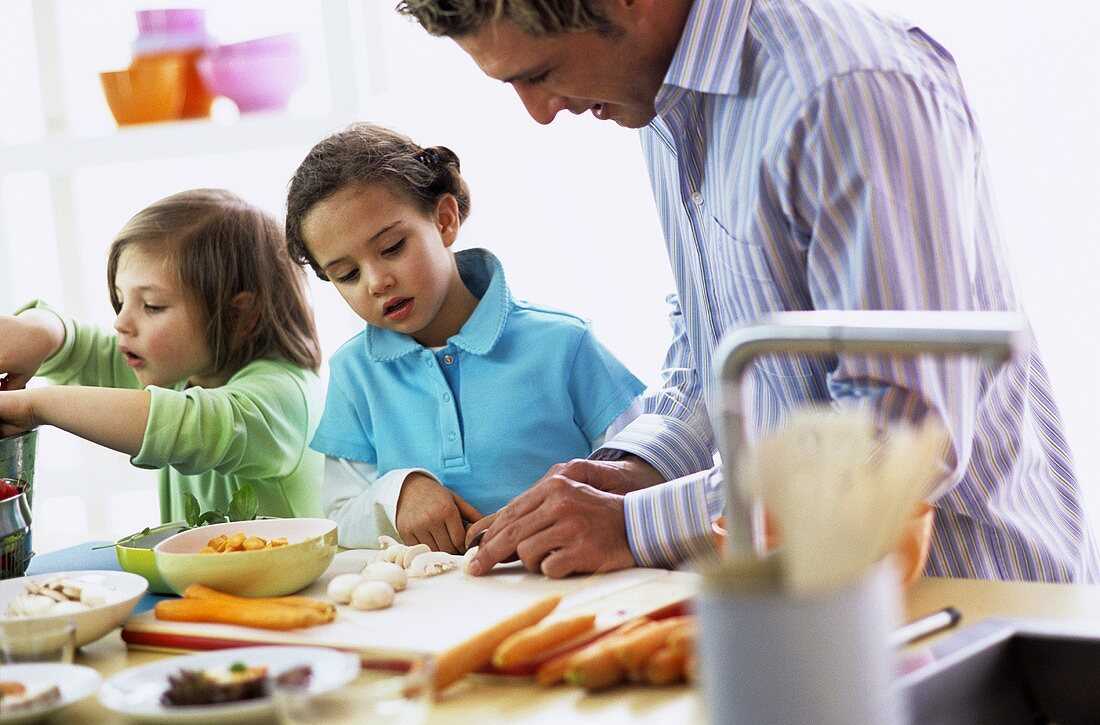Father with children (4-7) preparing meal