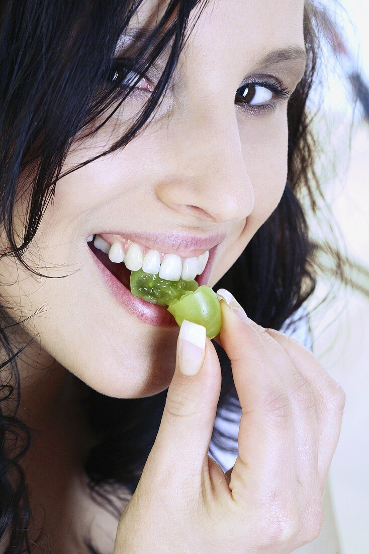 Young woman eating grape
