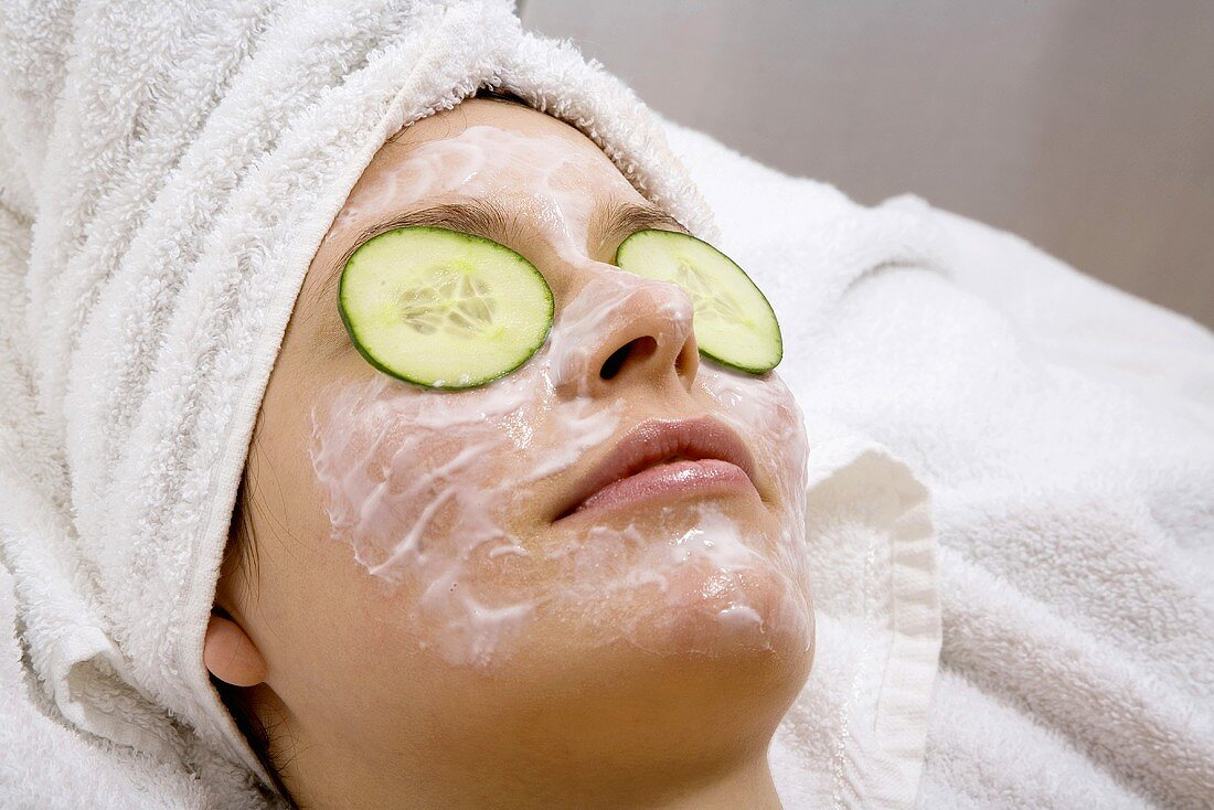 Young woman with face mask and cucumber slices