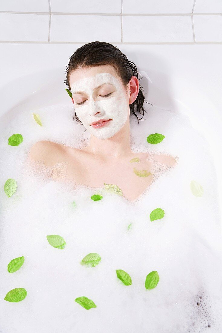 Young woman with face mask taking a bubble bath, eyes closed