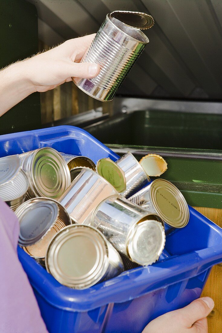 Person putting tin into refuse container